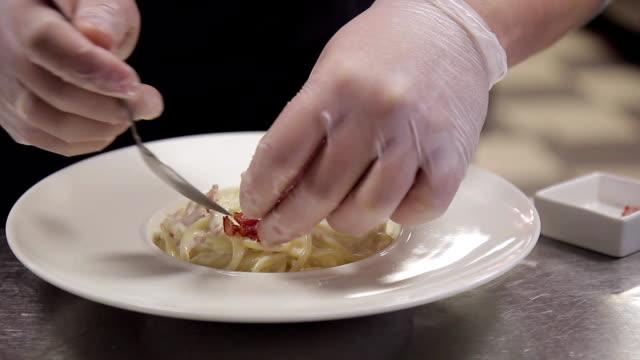 chef homme habillé en uniforme noir décorer la salade de pâtes industrielles - Vidéo