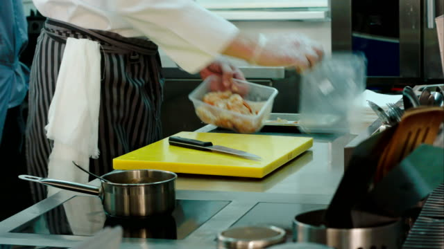 Male chef getting shrimps from container and putting them on a tray video