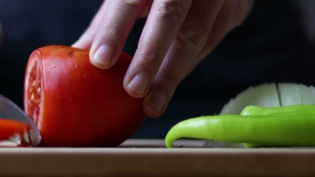 vídeos y material grabado en eventos de stock de el chef masculino está cortando tomate en tabla de cortar - pimiento verde
