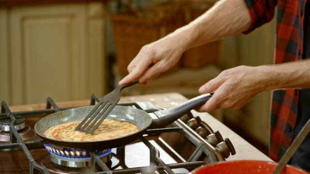 LD male chef making crepes in a cooking show and flips them into the air Medium locked down shot of a male chef  in a cooking show making crepes and he flips a crepe frying in the pan on the stove. Shot in Slovenia. frying pan stock videos & royalty-free footage