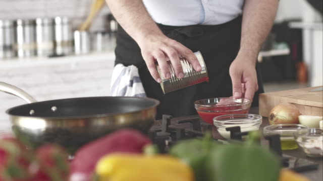 Male chef pouring chopped tomato from the food can video