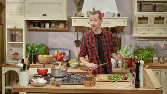 male chef preparing a vegetable soup on a cooking show - mostrare video stock e b–roll