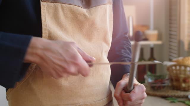 vídeos y material grabado en eventos de stock de chef masculino afilando cuchillo de carnicero en la cocina - aleación
