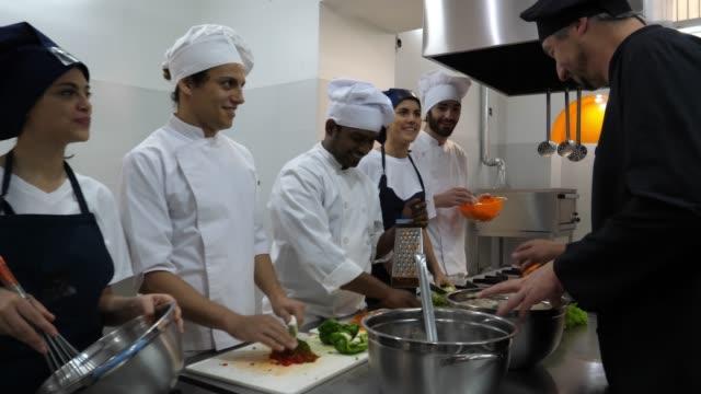 stockvideo's en b-roll-footage met mannelijke chef-kok onderwijs zijn leerlingen over de verschillende ingrediënten en hen aan te moedigen om te ruiken - dranken en maaltijden