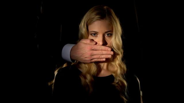 mężczyzna zamykający usta kobiety ręką, pani trzymająca dolary, niewolnictwo seksualne - cisza filmów i materiałów b-roll