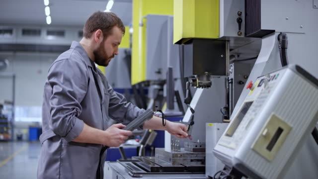 vidéos et rushes de opérateur d'un cnc masculin ds utilisant un contrôleur pour faire fonctionner une machine - machinerie
