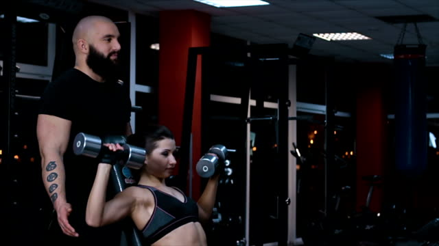Male coach helping young woman with dumbbell exercise during workout in gym Male coach helping young woman with dumbbell exercise during workout in gym prop stock videos & royalty-free footage