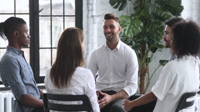 Male coach psychologist talking sitting in circle during group therapy Smiling male coach psychologist talk to diverse people patients group sit in circle at therapy session, counselor therapist help with problems at psychotherapy rehab meeting business training concept prop stock videos & royalty-free footage