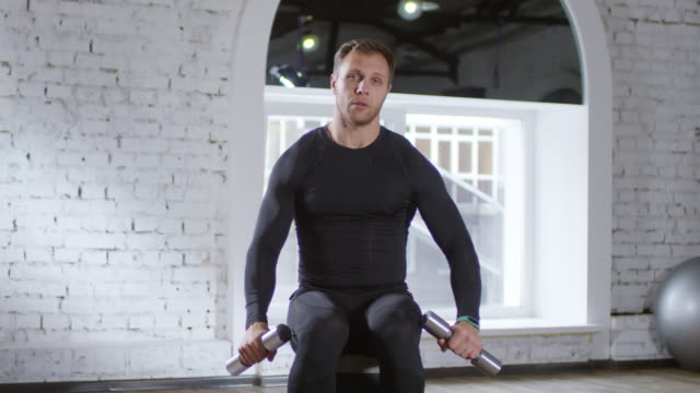 allenatore maschile che mostra esercizi con manubri sulla fotocamera - allenatore video stock e b–roll