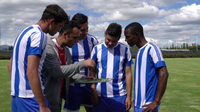stockvideo's en b-roll-footage met mannelijke coach praten over spel strategieën voor zijn gevarieerde team voordat u begint met een voetbalwedstrijd - huddle