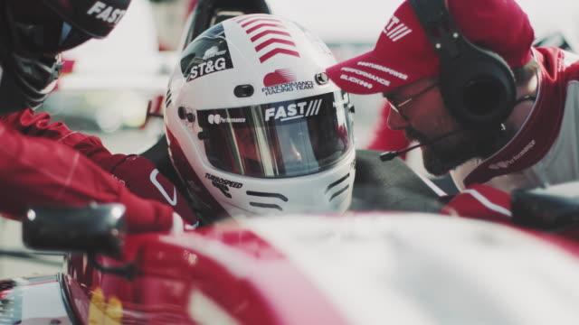 male coach talking with driver at pit stop - mechanik filmów i materiałów b-roll
