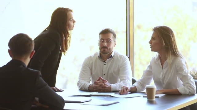 male colleague set apart angry businesswomen argue fight at meeting - rivalità video stock e b–roll