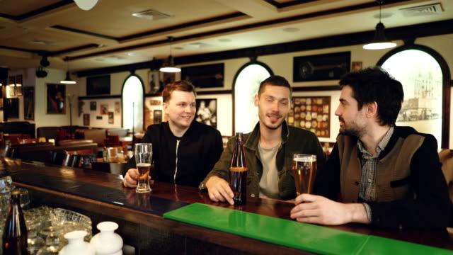 Colegas masculinos tienen conversación en el bar local. Compañeros de trabajo encuentro fuera de lugar de trabajo y comunicación informal. Interior bonito pub en fondo. - vídeo