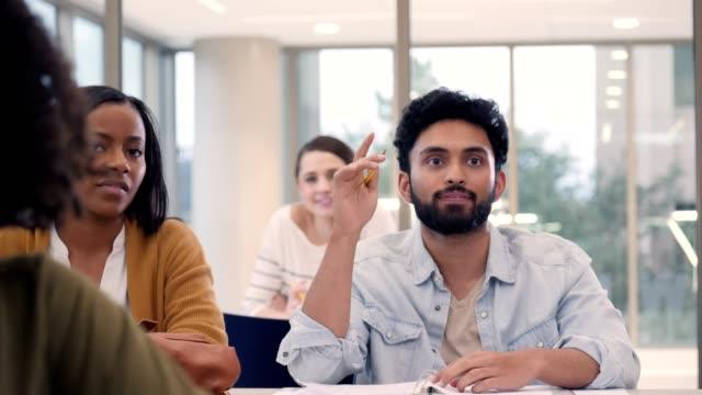vídeos de stock e filmes b-roll de male college student asks question during class - braços no ar