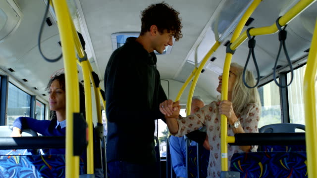 Male commuter helping mature commuter to get up while travelling in bus 4k