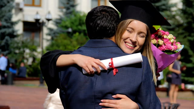 male congratulating sister with graduation day and presenting bouquet of flowers - compagni scuola video stock e b–roll