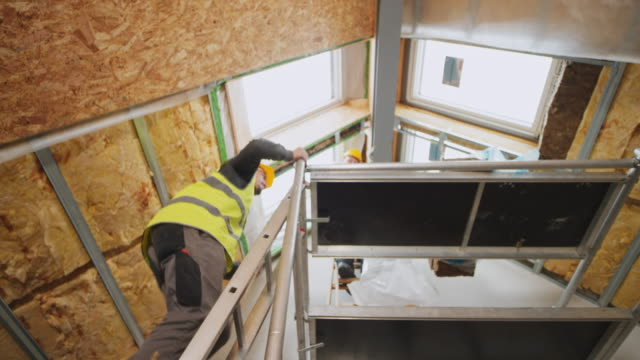 male construction worker climbing up a scaffold - soffitto video stock e b–roll