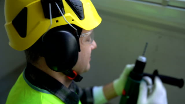 Male construction worker drilling concrete wall with a drill and smiling at the camera video