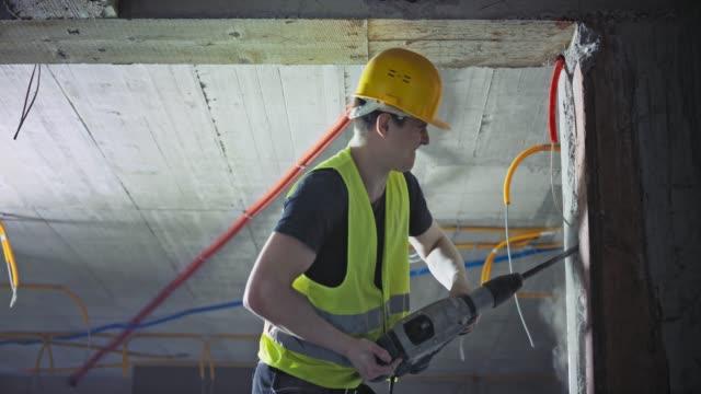 vídeos y material grabado en eventos de stock de ld hombre trabajador de la construcción haciendo un agujero en la pared para las tuberías con un martillo neumático - material de construcción
