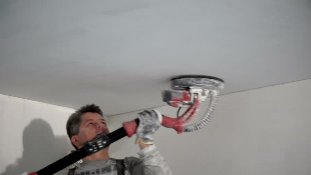 Male construction worker smoothing ceiling surface with sanding machine