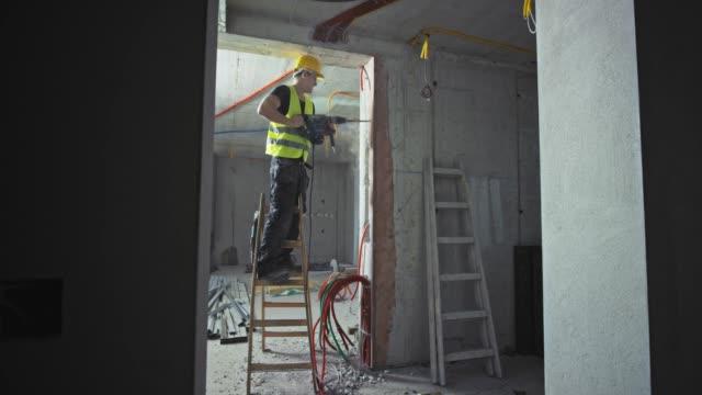 vídeos de stock, filmes e b-roll de trabalhador da construção masculino de ds que usa um jackhammer ao estar na escada dentro de um edifício - eletricista