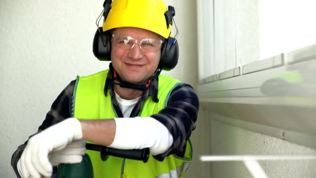 Male construction worker with a drill is smiling at the camera video