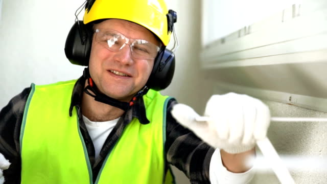 Male construction worker with a drill smiling at the camera. Slow motion video