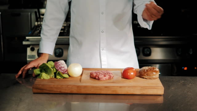 Male cooking chief in white robe drips coarse salt on uncooked meat video