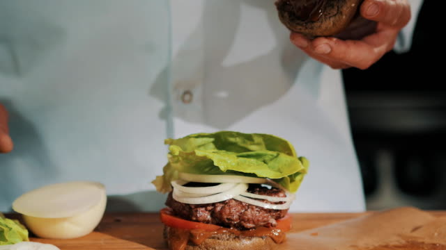 Male cooking chief in white robe finishes making hamburger and takes it in hands video