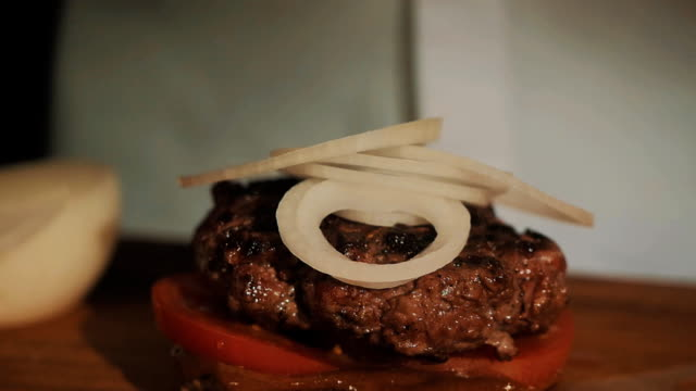 Male cooking chief in white robe making hamburger puts green salad on onion video