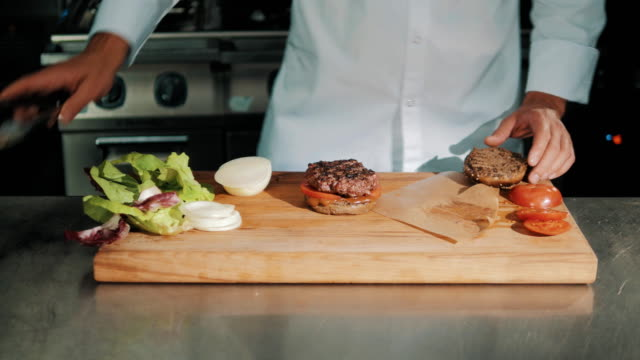 Male cooking chief in white robe making hamburger, puts grilled meat video