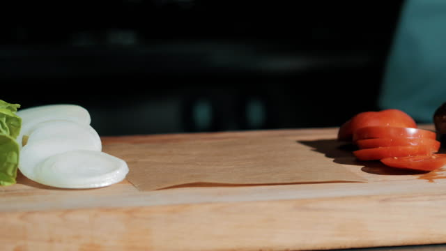 Male cooking chief in white robe puts cooked meat on wooden cutting board video
