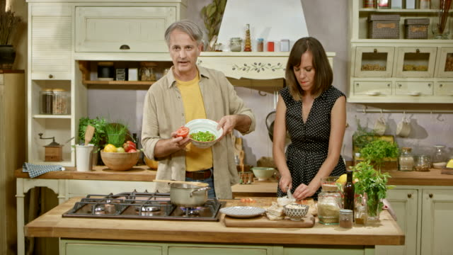 ds male cooking show host talking about the preparation of the food while female chef is cutting onions - mostrare video stock e b–roll