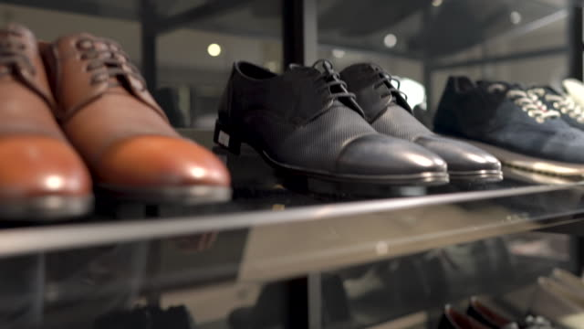 A male costumer taking classic style black pair of leather shoes in luxury business fashion boutique. Top bottom camera shot