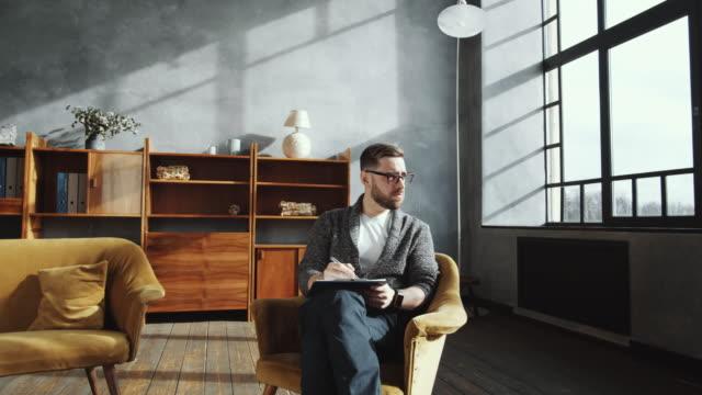 안락의자에 앉아 클립보드에 메모를 하는 남성 상담사 - 중년 남자 스톡 비디오 및 b-롤 화면