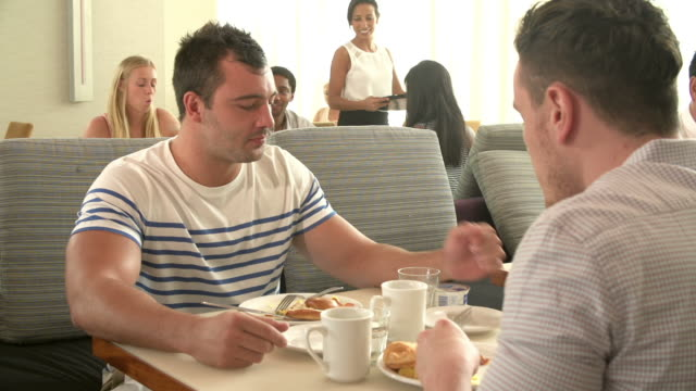Male Couple Enjoying Breakfast In Hotel Restaurant Male couple sitting in hotel restaurant eating breakfast and talking.Shot on Sony FS700 at frame rate of 25fps gay man stock videos & royalty-free footage