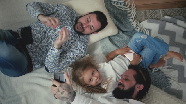 Male Couple Taking Selfies With Daughter On The Floor