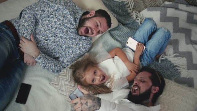 Male Couple Taking Selfies With Little Daughter