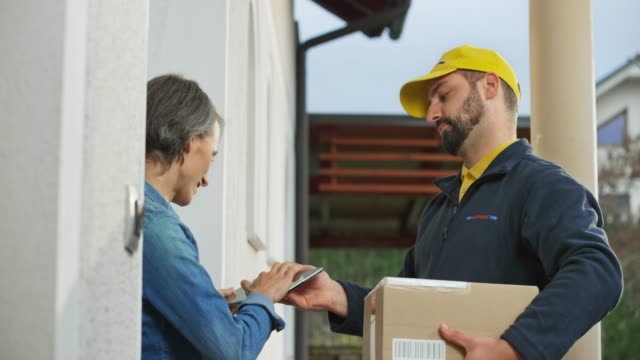 Male courier delivering a package to a woman