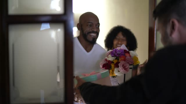 Male courier delivering flower and presents to a couple at their front door