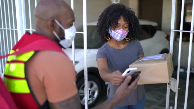 vídeos de stock e filmes b-roll de male courier delivering packages to woman at her front door - with face mask - afro latino mask