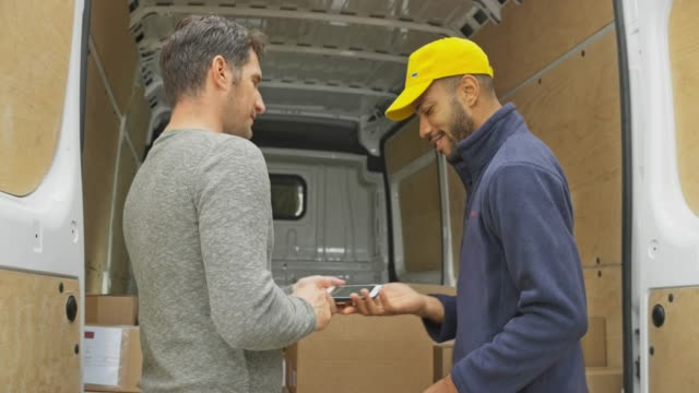 Male courier giving the male customer a POD to sign before handing him the package