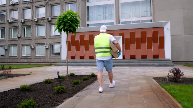 Male courier, in protective mask, gloves, goes through courtyard of hospital or medical facility, carries cardboard boxes, parcels. Cargo delivery service during coronavirus outbreak, quarantine video