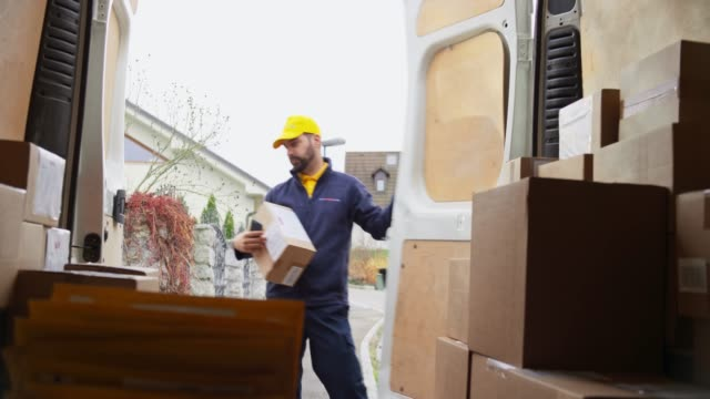 male courier scanning a package and walking out of the van - furgone video stock e b–roll