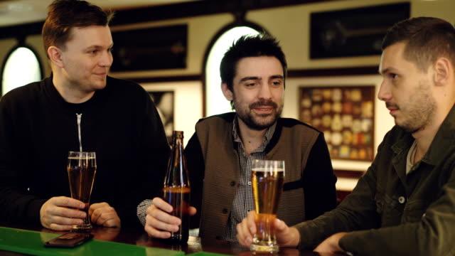 Compañeros de trabajo masculinos tienen conversación en el bar local. Jóvenes se reúnen fuera de lugar de trabajo y comunicación informal, tintineo de vasos y bebiendo cerveza. - vídeo
