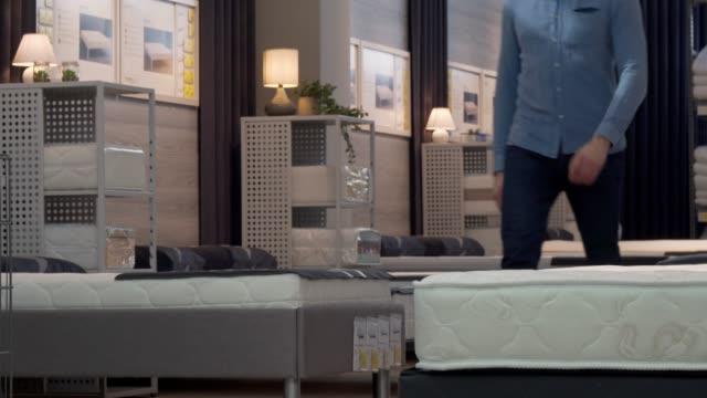 stockvideo's en b-roll-footage met mannelijke klant kiezen orthopedische matras en bed op meubelwinkel - comfortabel