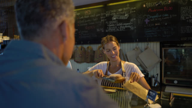 stockvideo's en b-roll-footage met mannelijke klant betaalt voor een object in gebak met een credit card en het te houden tot de credit card reader als serveerster hem vertelt - bakery