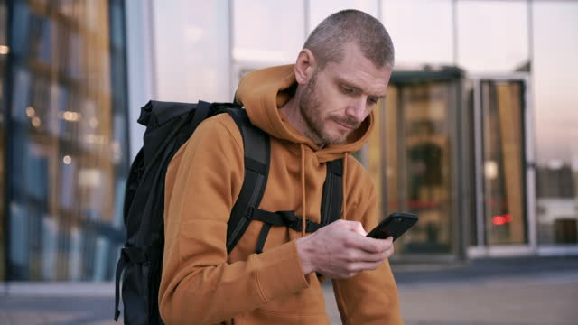 A male cyclist in a red hoodie and carrying a backpack is holding a phone and typing A male cyclist in a red hoodie and carrying a backpack is holding a phone and typing treedeo speed way stock videos & royalty-free footage