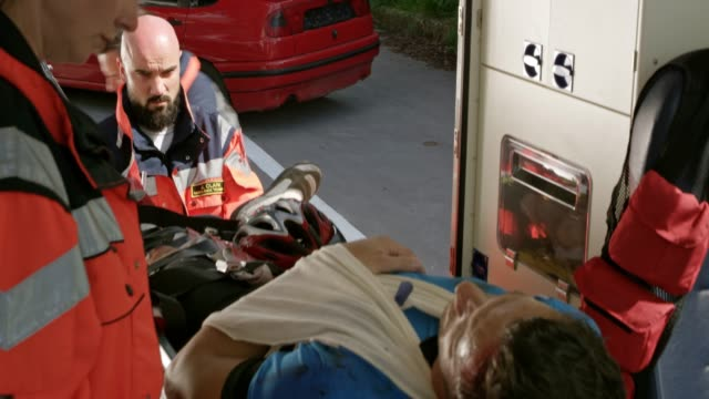 Male cyclist injured in a accident being loaded into the ambulance on a stretcher Medium handheld shot of an injured male cyclist being loaded into the ambulance while lying secured on the stretcher. Shot in Slovenia. stretcher stock videos & royalty-free footage
