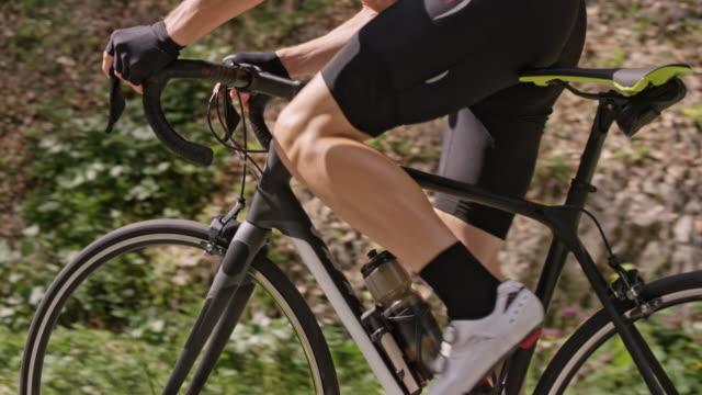 slo mo male cyclist riding his road bike up a road in nature - ciclismo su strada video stock e b–roll